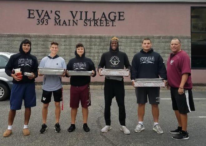 Wayne Hills football players: (from left) seniors Gabe Dellechiaie, Tom Sharkey, Anthony Pontolillo, Charles Njoku and Bence Polgar, along with coach Wayne Demikoff, helped donate food to Eva's Village on Oct. 6.