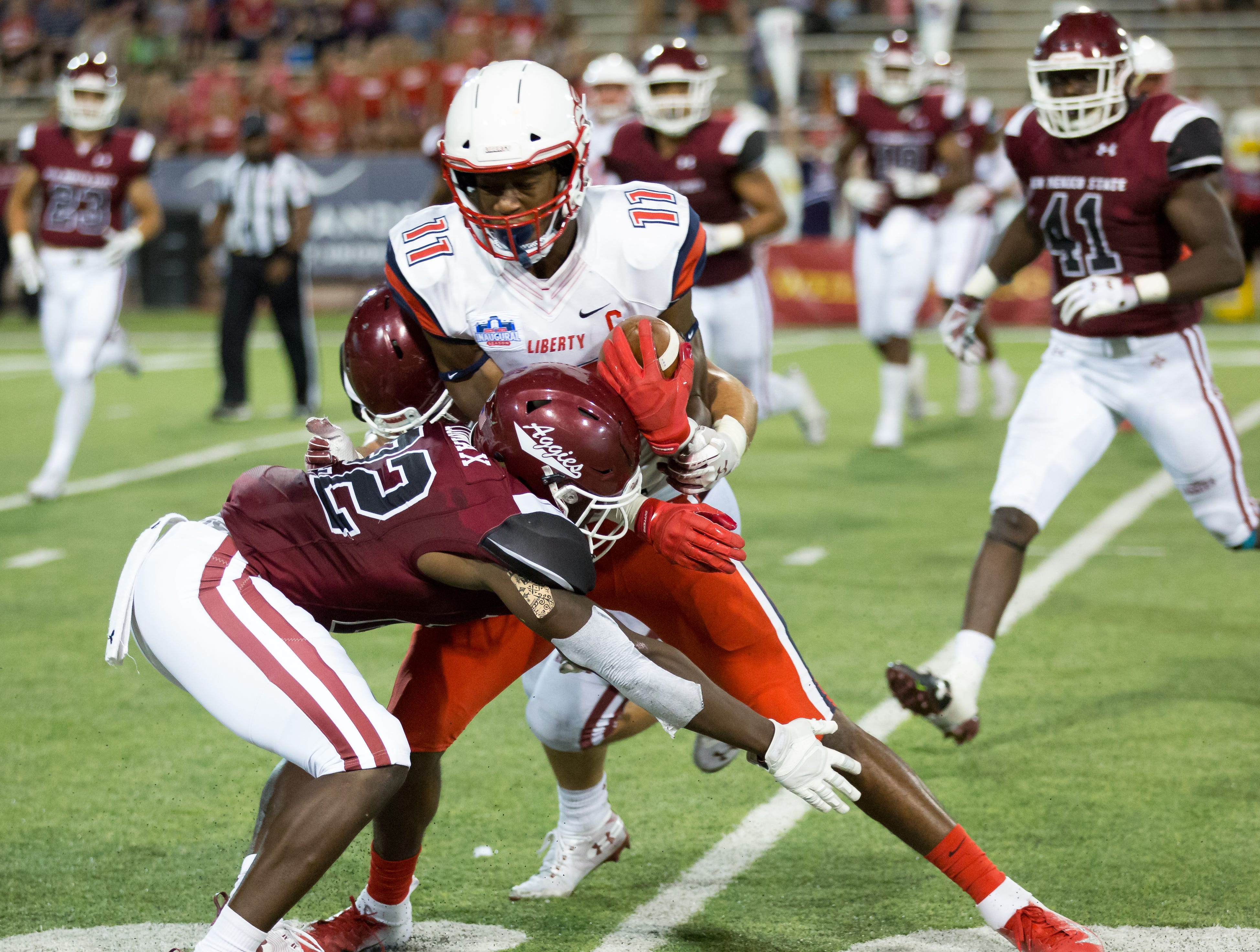 Liberty's Antonio Grandy-Golden is wrapped up by NMSU's Shamad Lomax on Saturday, Oct. 6, 2018 at Aggie Memorial Stadium.