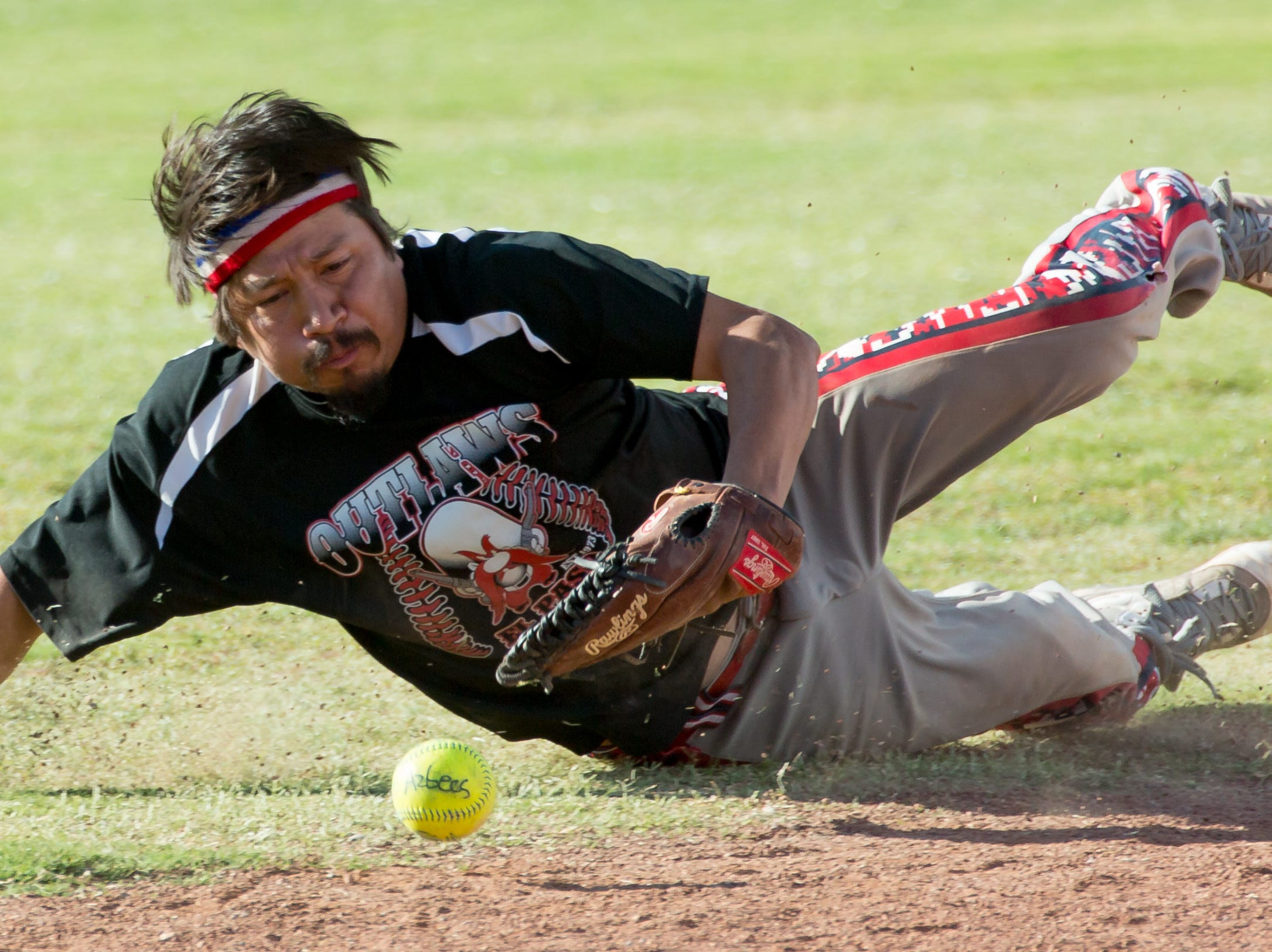 Outlaws team member Lucas Quimiro, of El Paso, Texas, dives on the ground for the ball  on Sunday, Oct. 7, 2018 during the 39th Whole Enchilada Invitational softball tournament at the Hadley complex.