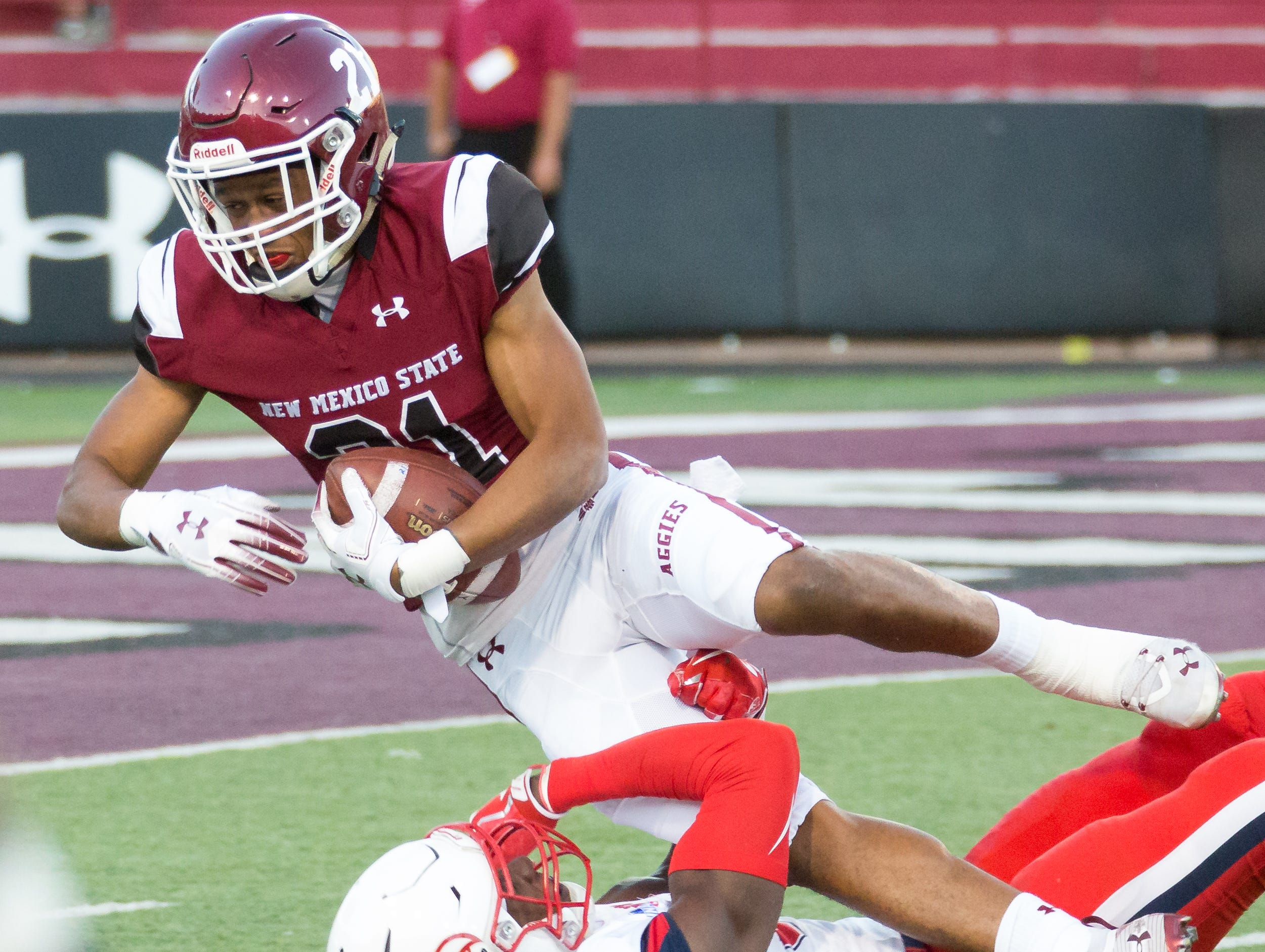 New Mexico State University's Anthony Muse grabs the ball while Liberty's Elijah Benton works on bringing him down on Saturday, Oct. 6, 2018 at the Aggie Memorial Stadium.