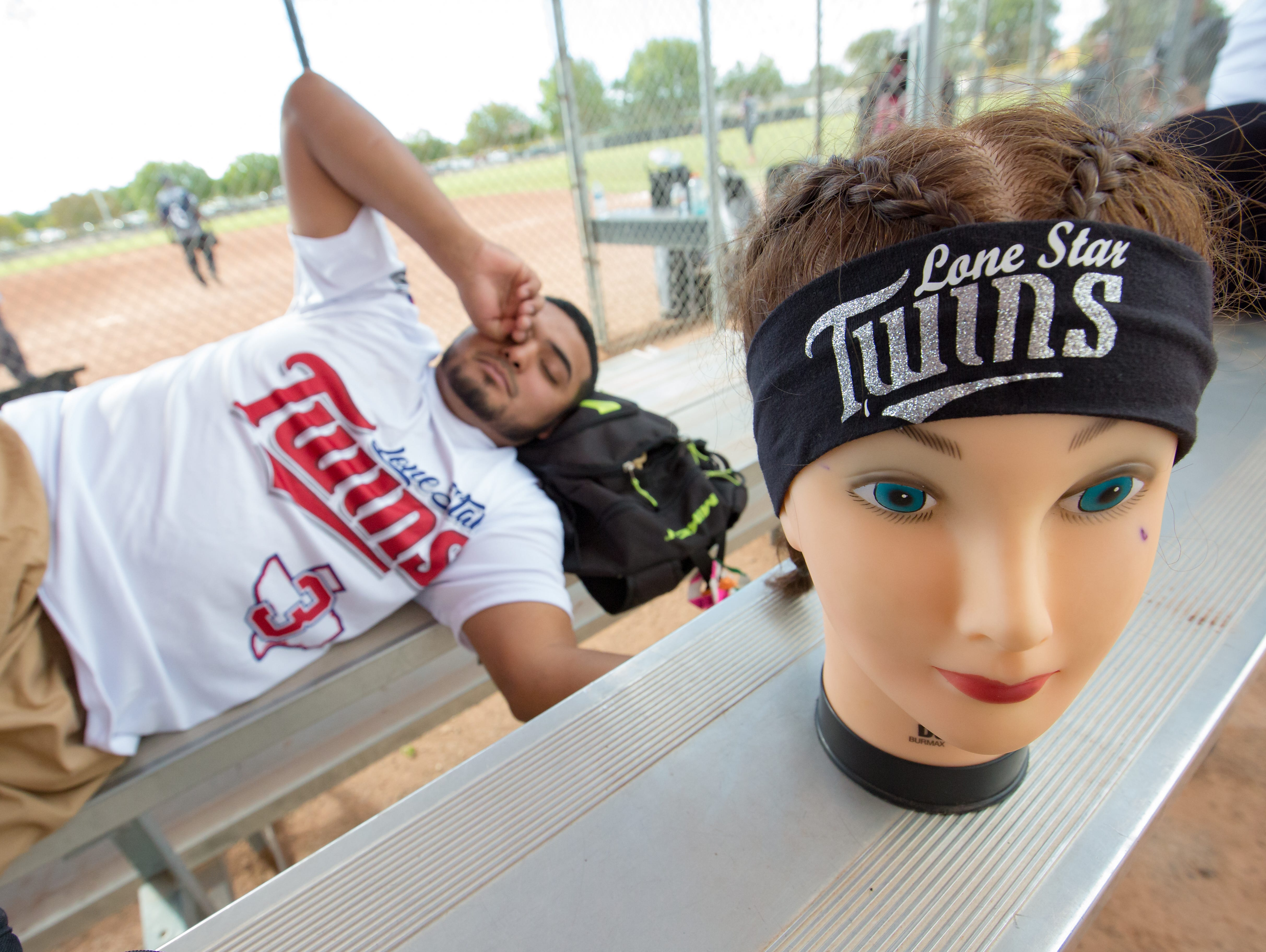 Lone Star Twins team member, Hector Gallegos, of Corpus Christi, Texas stretches while he naps before tournament play on Sunday, Oct. 7, 2018 during the 39th Whole Enchilada Invitational softball tournament at the Hadley complex. Pictured next to Gallegos is the team mascot, Deb.