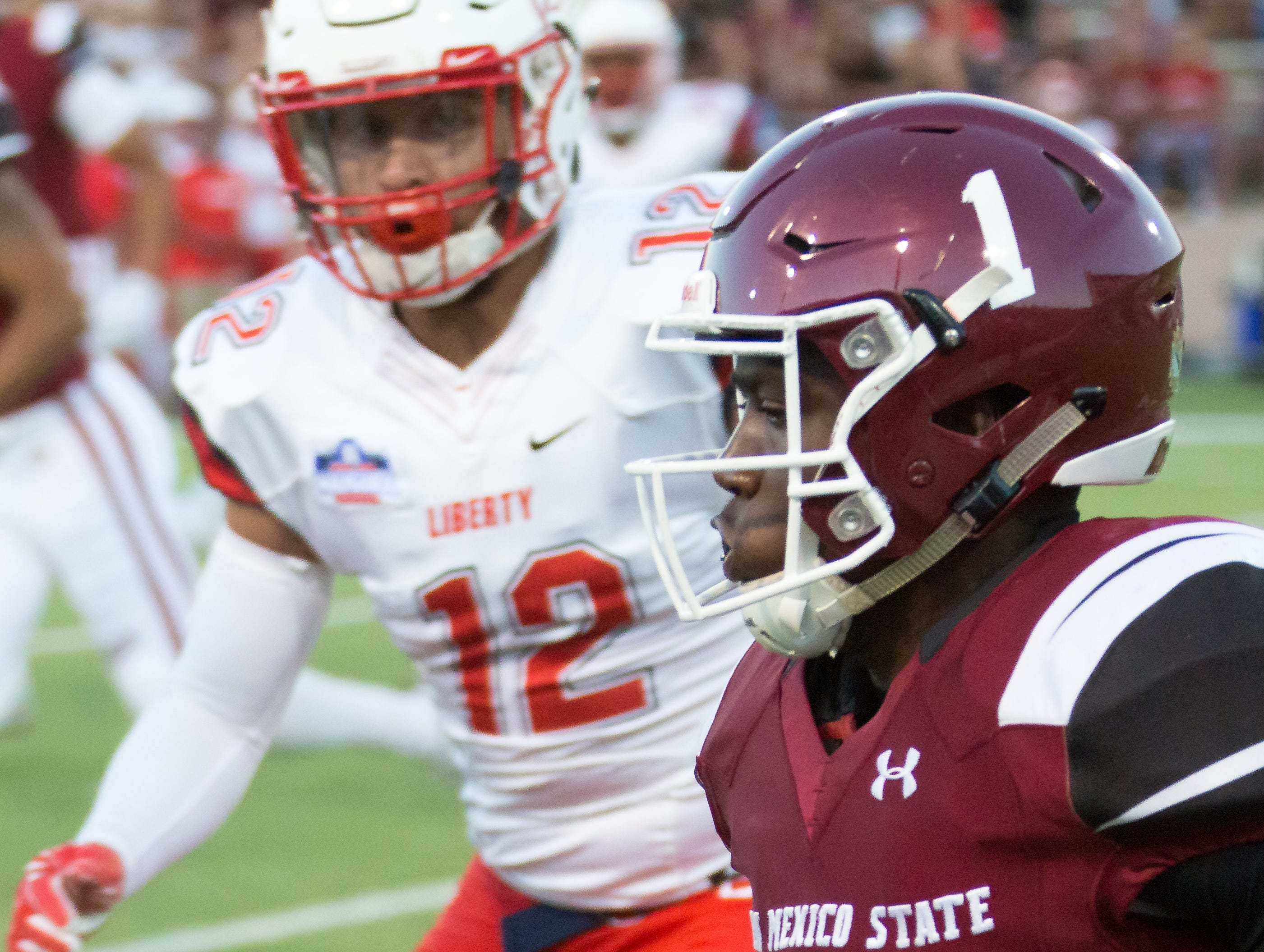 NMSU's Jason Huntley runs for some yards as Liberty's Brandon Tillmon closes in on