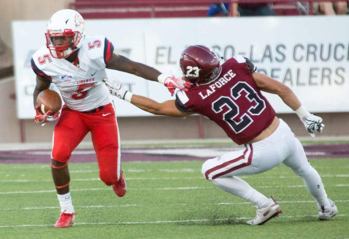 Liberty's DJ Stubbs runs with the ball as NMSU'd Ron LaForce tries to make the stop on Saturday, Oct. 6, 2018 at Aggie Memorial Stadium.