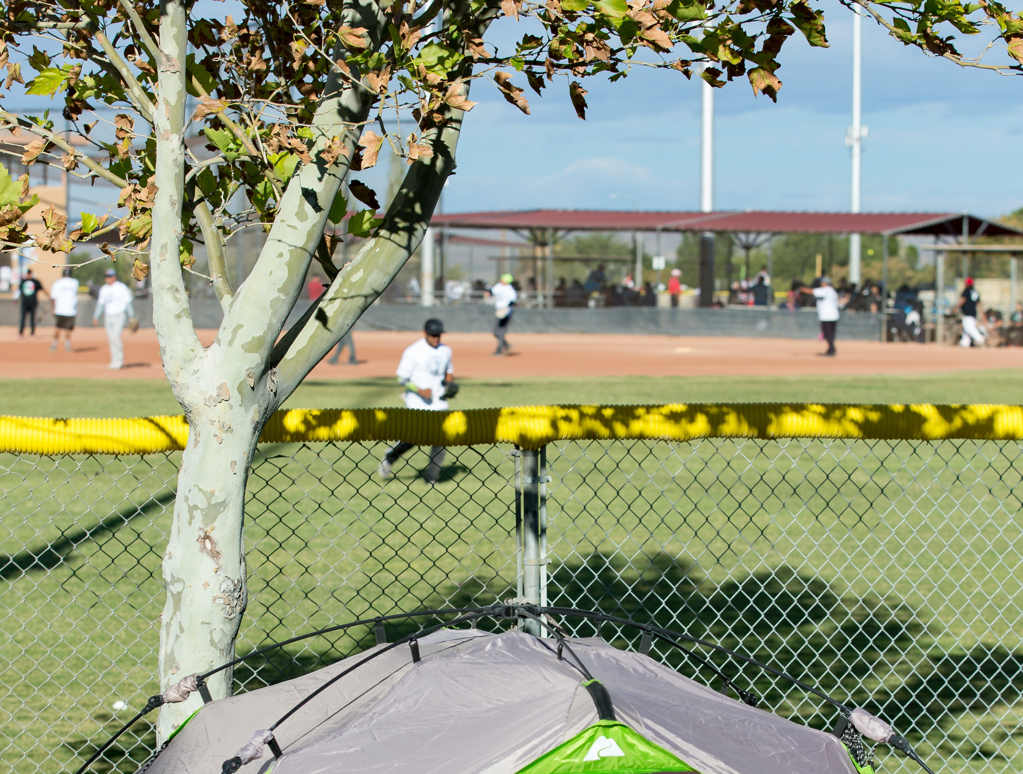 Jacen Brown, 11, of El Paso, Texas, sleeps in his tent while tournament play continues in the background  on Sunday, Oct. 7, 2018 during the 39th Whole Enchilada Invitational softball tournament at the Hadley complex.
