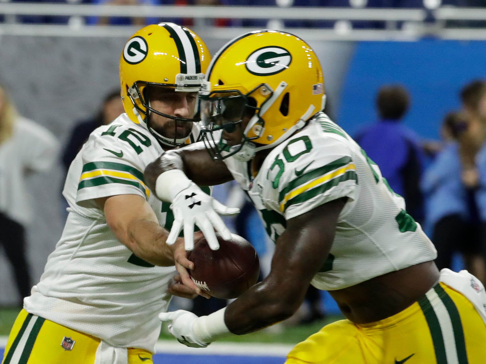 Green Bay Packers quarterback Aaron Rodgers (12) hands off to Green Bay Packers running back Jamaal Williams (30) while warming up before the Green Bay Packers vs. Detroit Lions NFL game at Ford Field, Detroit, Sunday, October 7, 2018.