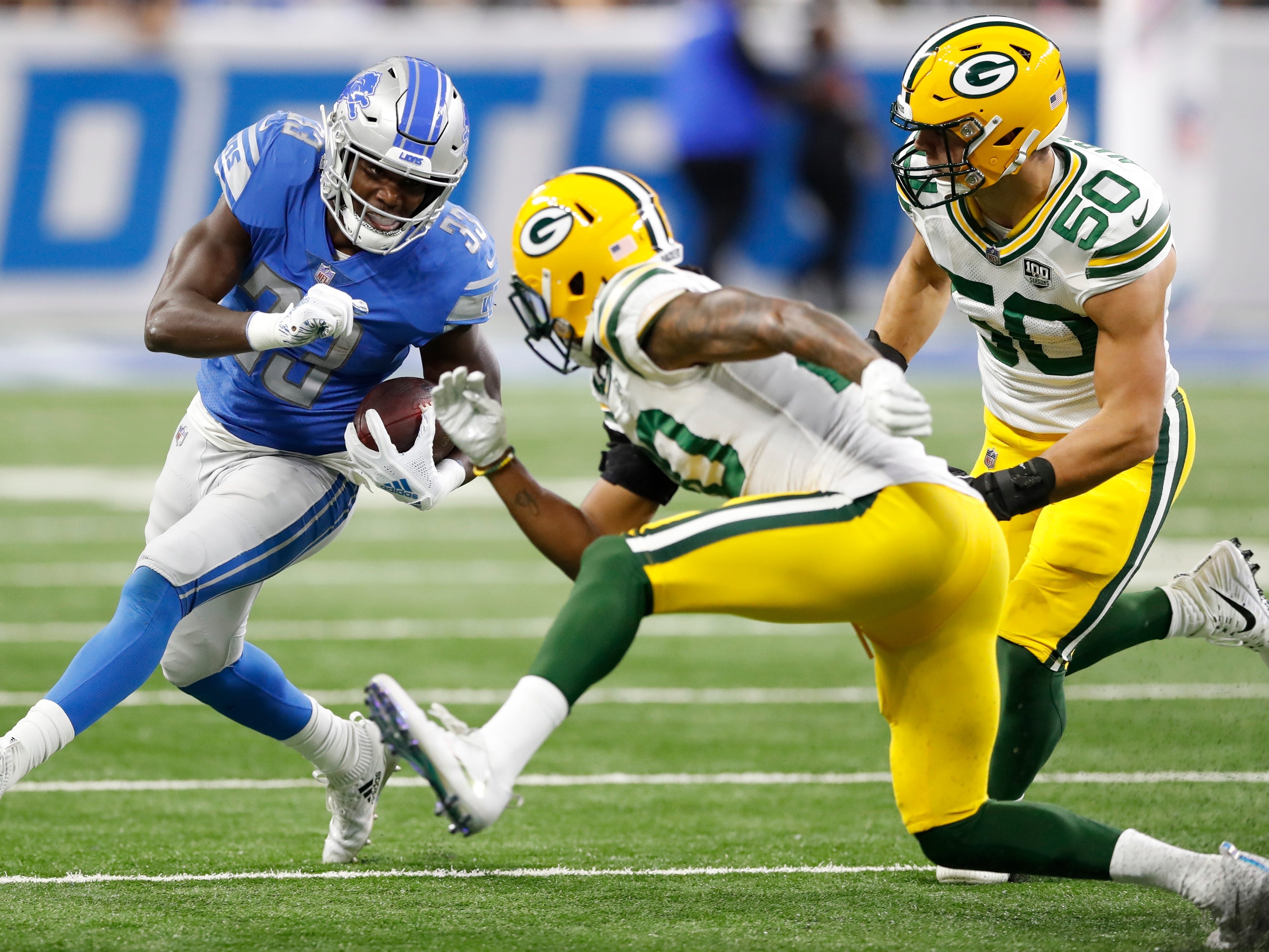 Green Bay Packers cornerback Kevin King (20) and linebacker Blake Martinez (50) close in on Detroit Lions running back Kerryon Johnson (33) during the first half of an NFL football game, Sunday, Oct. 7, 2018, in Detroit.