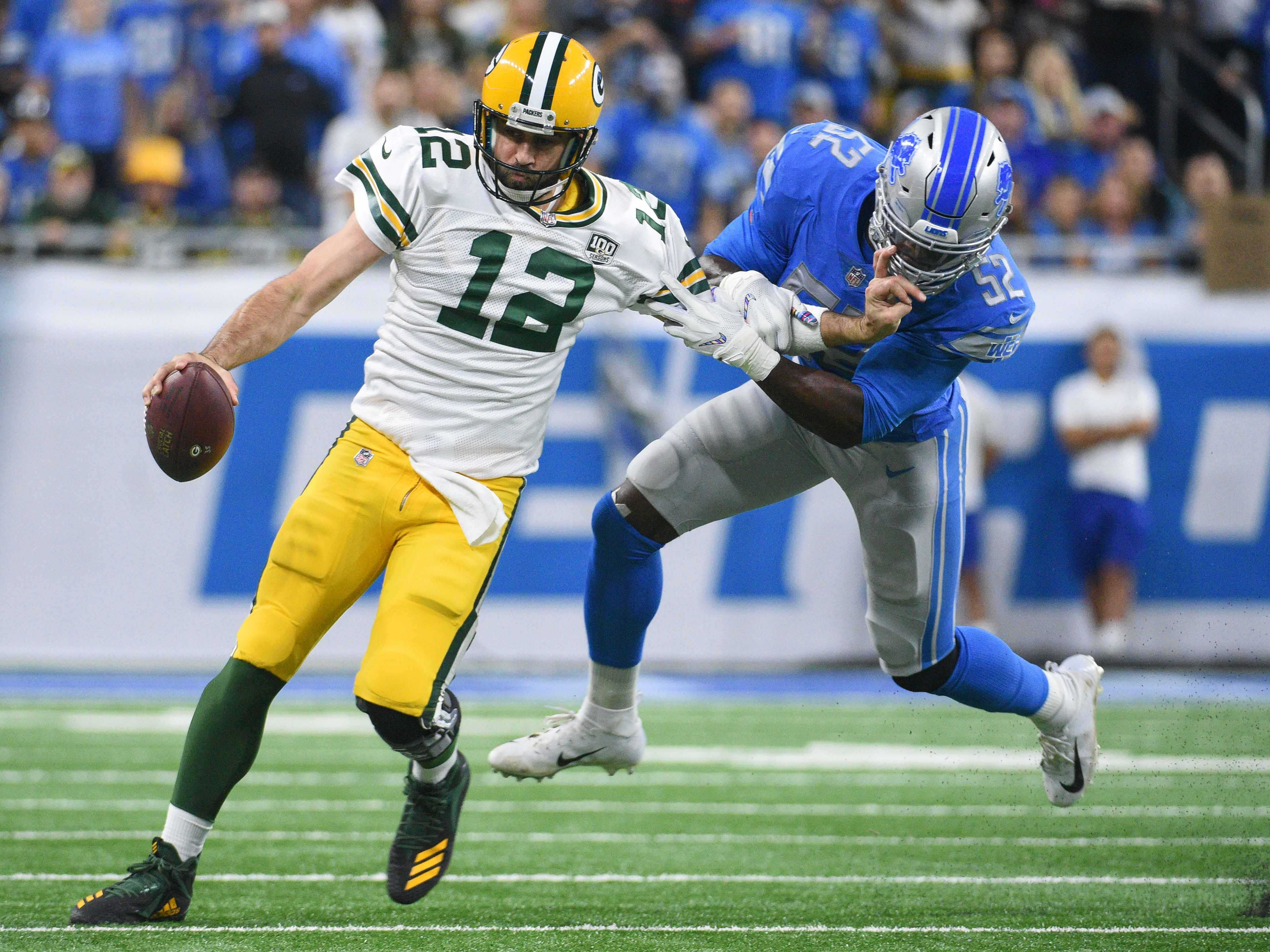 Oct 7, 2018; Detroit, MI, USA; Detroit Lions linebacker Christian Jones (52) attempts to tackle Green Bay Packers quarterback Aaron Rodgers (12) during the first quarter at Ford Field.