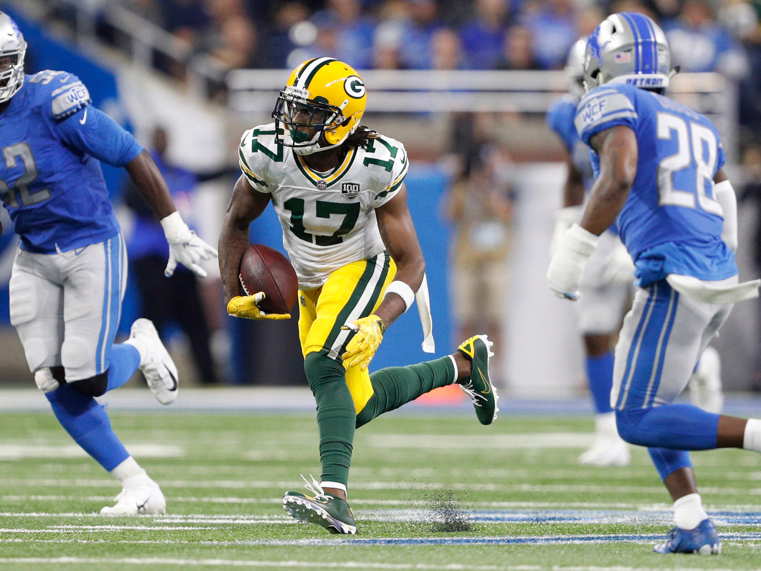 Oct 7, 2018; Detroit, MI, USA; Green Bay Packers wide receiver Davante Adams (17) runs after a catch against Detroit Lions strong safety Quandre Diggs (28) and linebacker Christian Jones (52) during the second quarter at Ford Field.