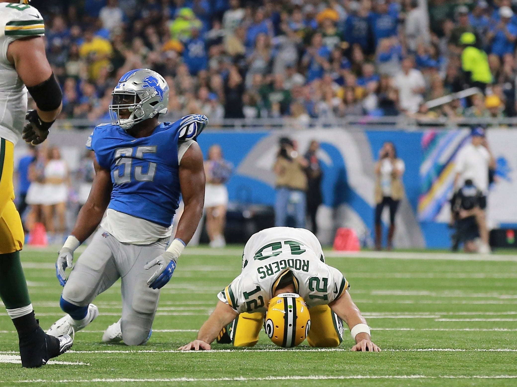 Green Bay Packers quarterback Aaron Rodgers (12) reacts after being tackled by Detroit Lions defensive end Romeo Okwara (95) during the first half of an NFL football game, Sunday, Oct. 7, 2018, in Detroit.