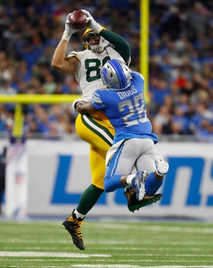 Green Bay Packers tight end Jimmy Graham (80), defended by Detroit Lions strong safety Quandre Diggs (28), makes a catch during the first half of an NFL football game, Sunday, Oct. 7, 2018, in Detroit.