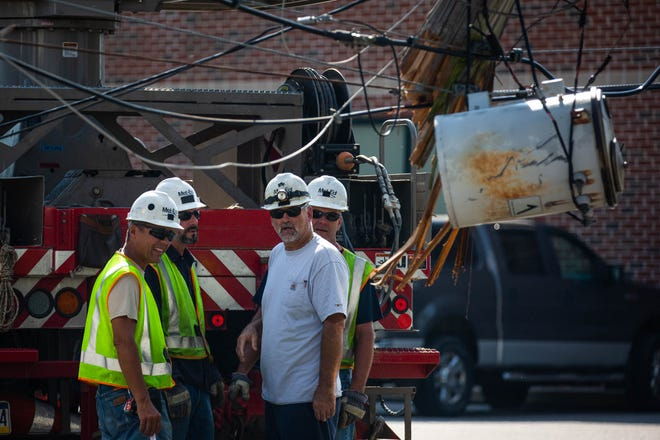 Workers from Met-Ed look toward a dangling electrical transformer as it hangs on wires at the scene of a single-vehicle crash with entrapment on the 1100 block of West Elm Ave., Sunday, Oct. 7, 2018, in Conewago Township. Two women were taken to York Hospital after the crash, said officials, one by medical helicopter and one by ambulance.