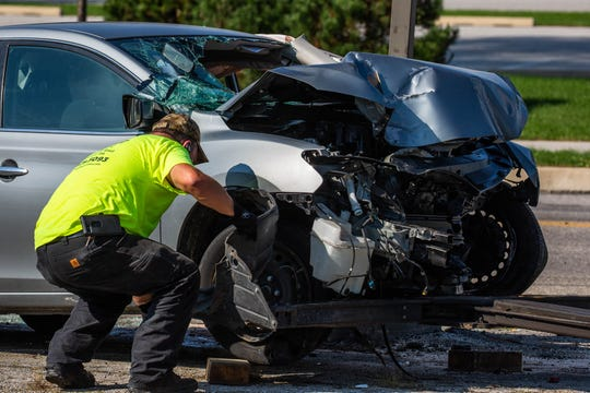 A tow truck worker prepares a wrecked sedan to be moved at the scene of a single-vehicle crash with entrapment on the 1100 block of West Elm Ave., Sunday, Oct. 7, 2018, in Conewago Township. Two women were taken to York Hospital after the crash, said officials, one by medical helicopter and one by ambulance.