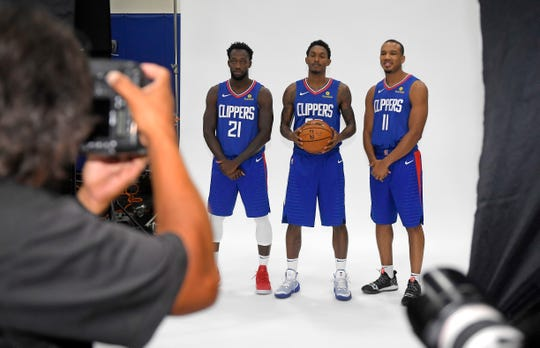 Los Angeles Clippers photographer Juan Ocampo, left, takes pictures of Patrick Beverley, second from left, Lou Williams, second from right, and Avery Bradley during media day at the NBA basketball team's practice facility Monday, Sept. 24, 2018, in Los Angeles. (AP Photo/Mark J. Terrill)