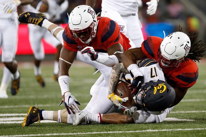 Arizona safety Troy Young (11) (left) and running back Gary Brightwell (23) tackle California wide receiver Vic Wharton III (17) during the first half of an NCAA college football game Saturday, Oct. 6, 2018, in Tucson, Ariz. (AP Photo/Chris Coduto)