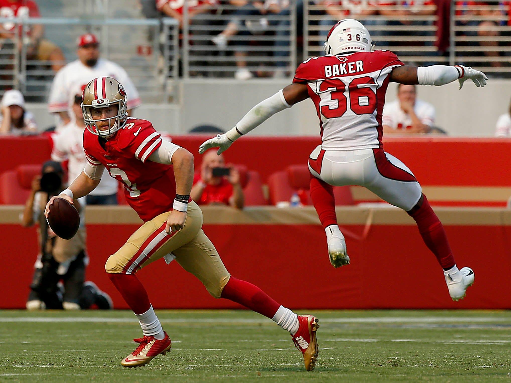 Oct 7, 2018; Santa Clara, CA, USA; San Francisco 49ers quarterback C.J. Beathard (3) eludes Arizona Cardinals defensive back Budda Baker (36) in the second quarter at Levi's Stadium.