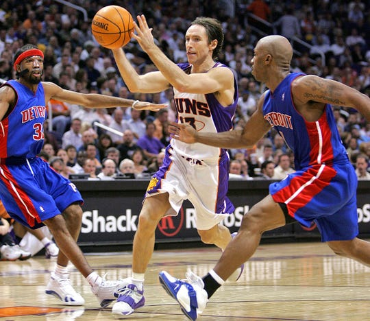 Steve Nash drives past the Pistons' Chauncey Billups (right) and Richard Hamilton in 2005.