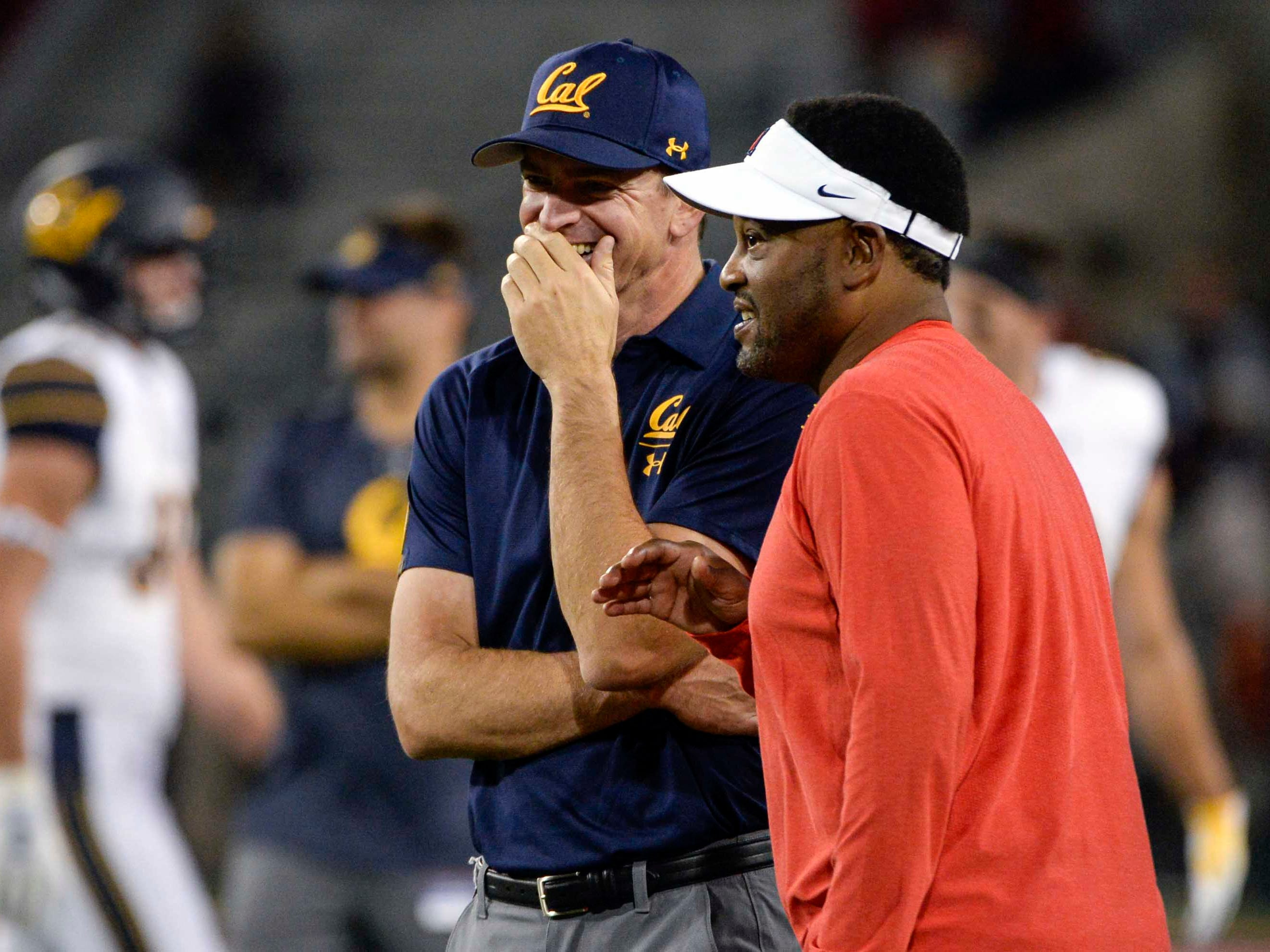 Oct 6, 2018; Tucson, AZ, USA; California Golden Bears head coach Justin Wilcox (left) and Arizona Wildcats head coach Kevin Sumlin talk before the game at Arizona Stadium. Mandatory Credit: Casey Sapio-USA TODAY Sports