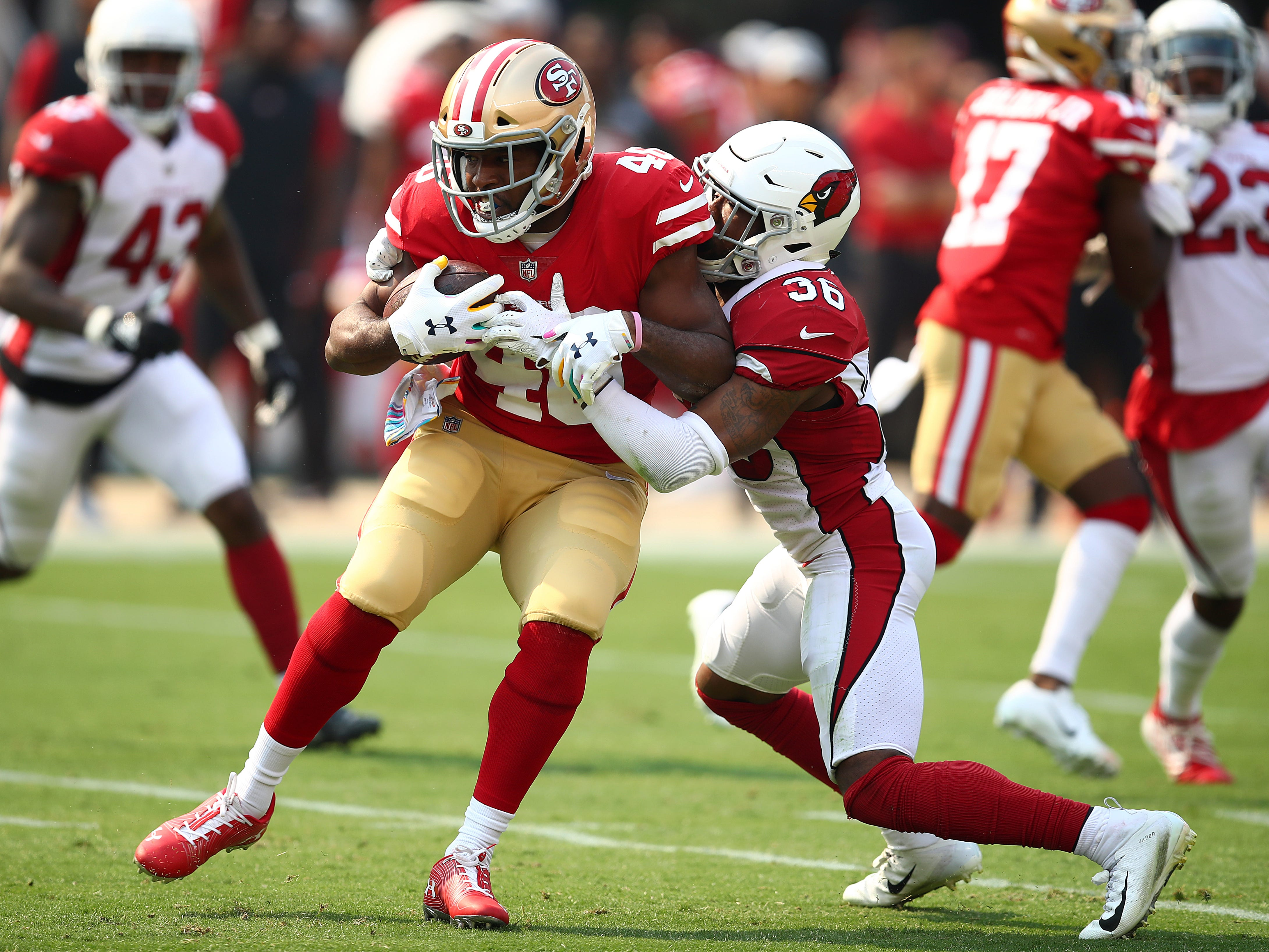 San Francisco 49ers running back Alfred Morris, left, runs against Arizona Cardinals safety Budda Baker (36) during the first half of an NFL football game in Santa Clara, Calif., Sunday, Oct. 7, 2018.