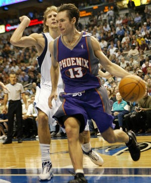 Phoenix Suns guard Steve Nash (13) from Canada drives past Dallas Mavericks forward Dirk Nowitzki, back, from Germany, in the fourth qyuarter of their game in Dallas, Tuesday, Nov. 16, 2004. The Suns won 107-101.