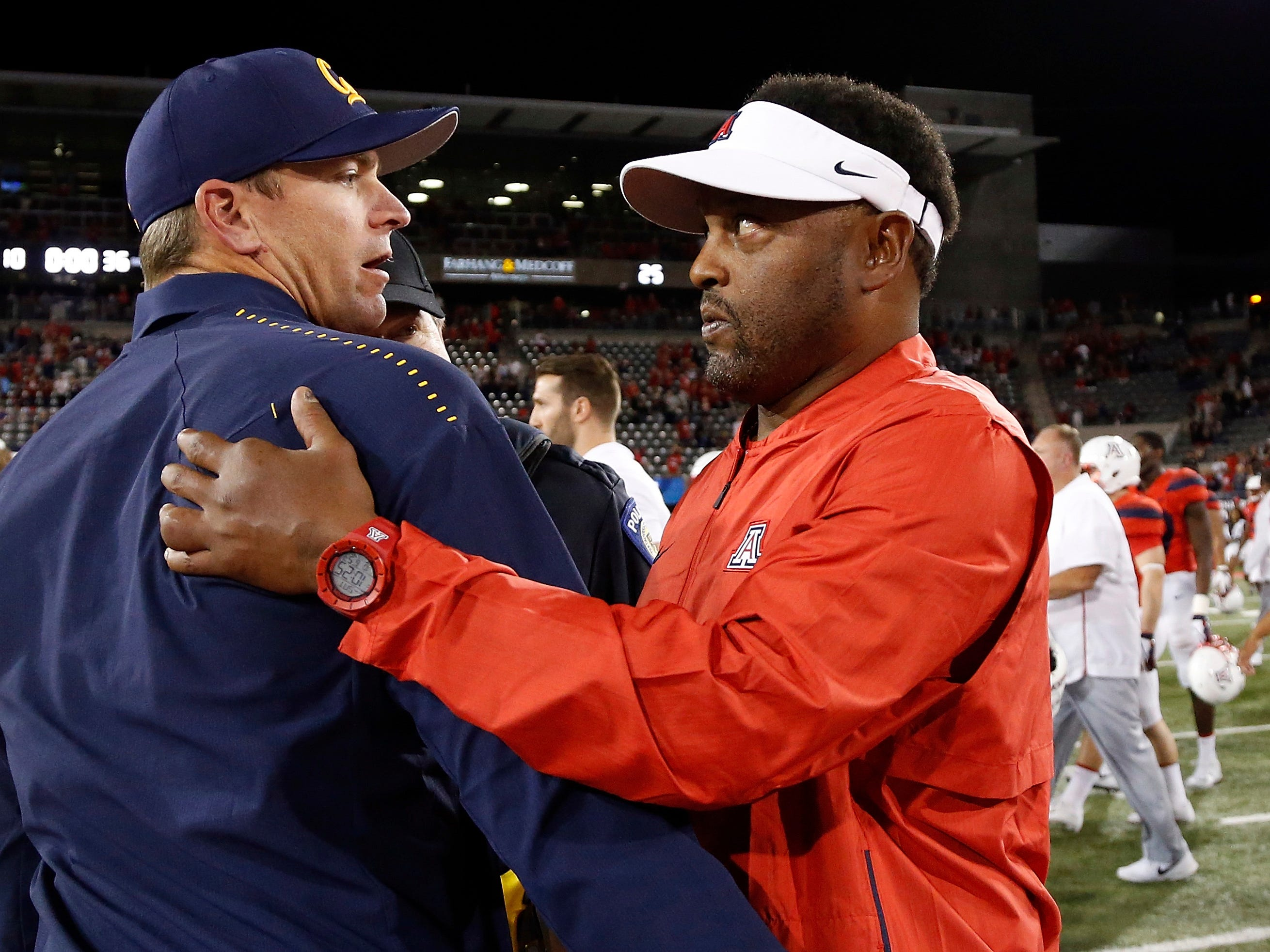 Arizona coach Kevin Sumlin, right, greets California coach Justin Wilcox after an NCAA college football game Saturday, Oct. 6, 2018, in Tucson, Ariz.