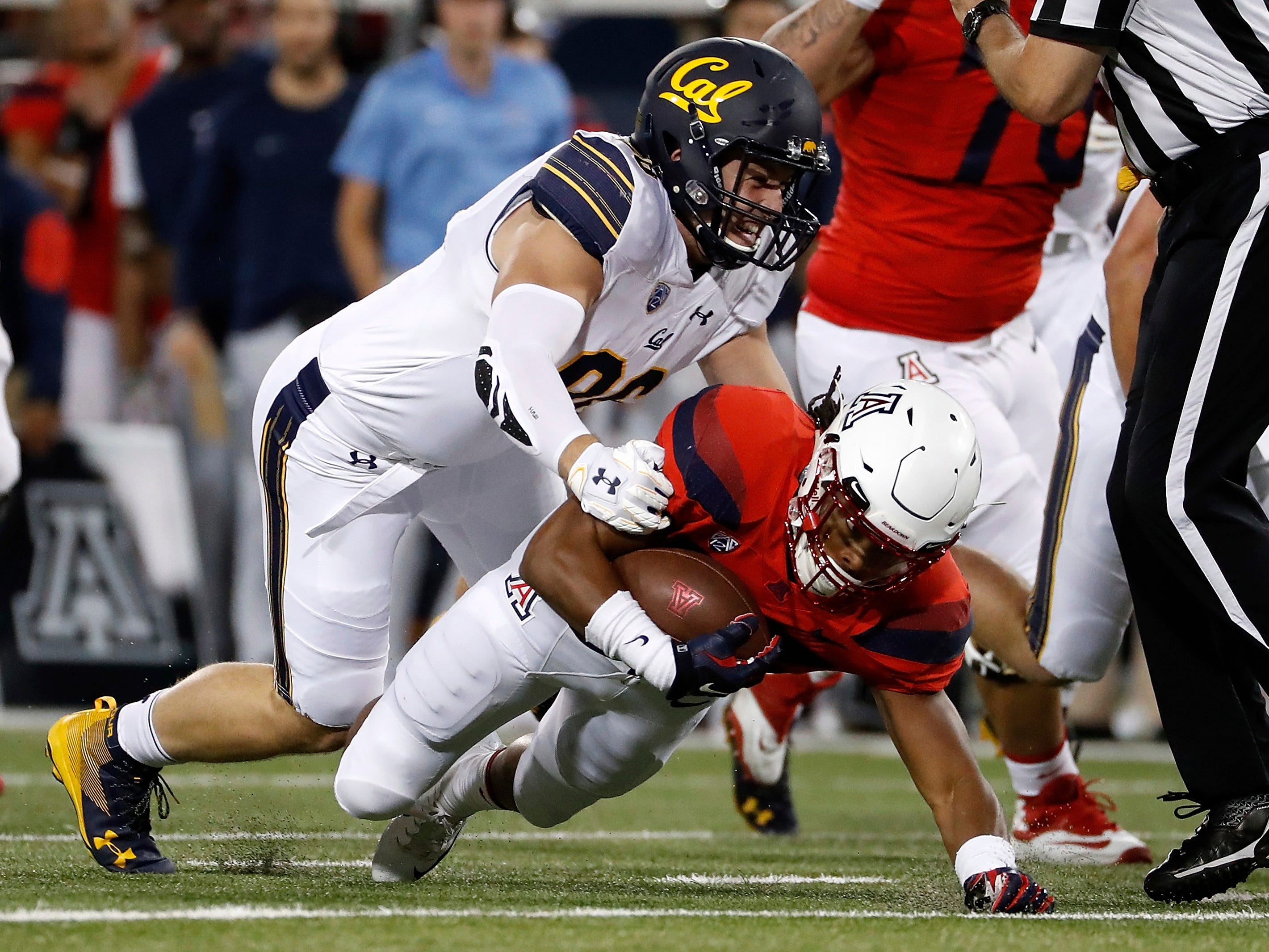 California defensive end Tevin Paul (96) tackles Arizona running back Gary Brightwell (23) during the first half of an NCAA college football game Saturday, Oct. 6, 2018, in Tucson, Ariz. (AP Photo/Chris Coduto)