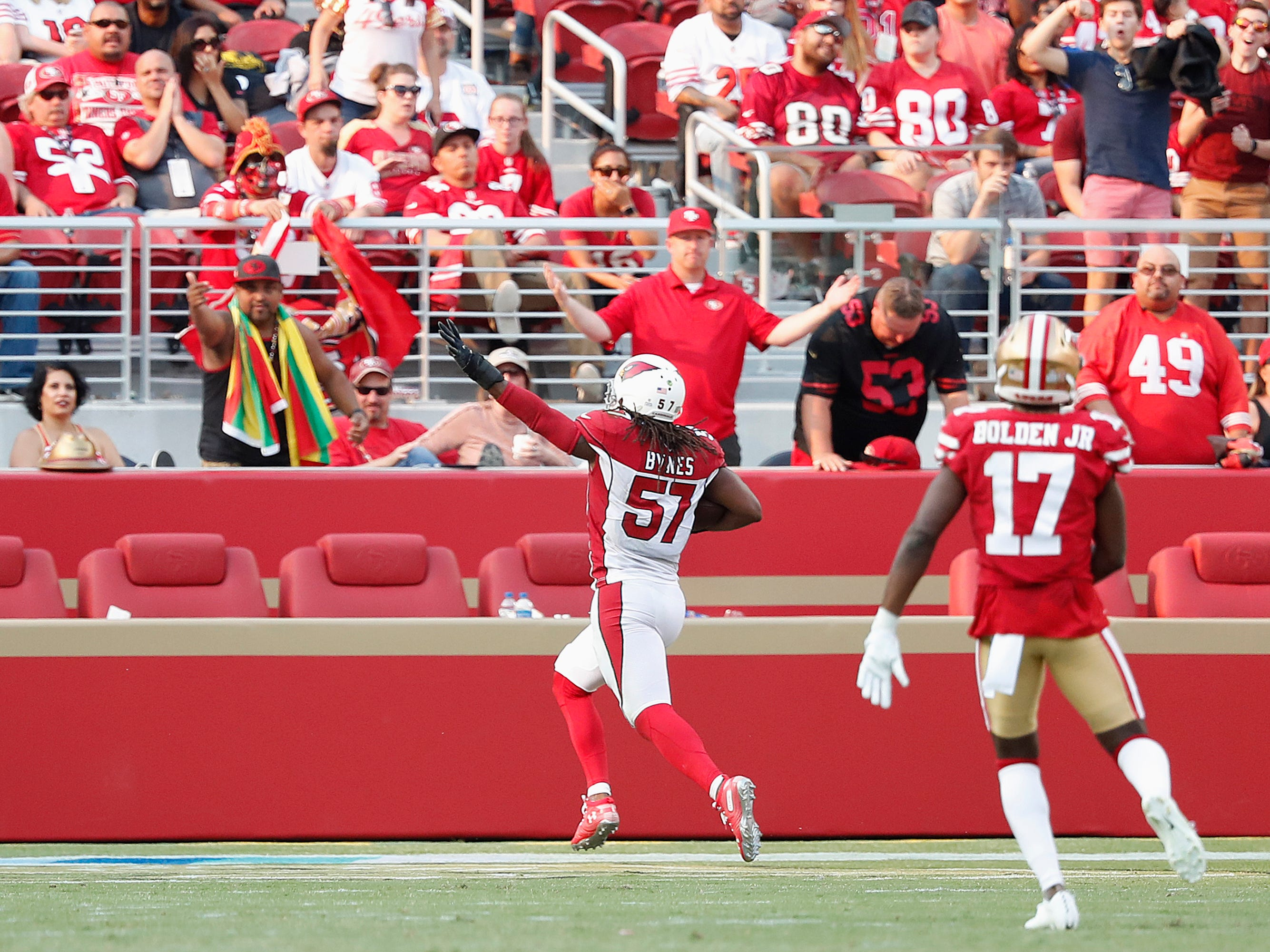 Arizona Cardinals linebacker Josh Bynes (57) scores a touchdown on a returned fumble in front of San Francisco 49ers wide receiver Victor Bolden Jr. (17) during the second half of an NFL football game in Santa Clara, Calif., Sunday, Oct. 7, 2018.