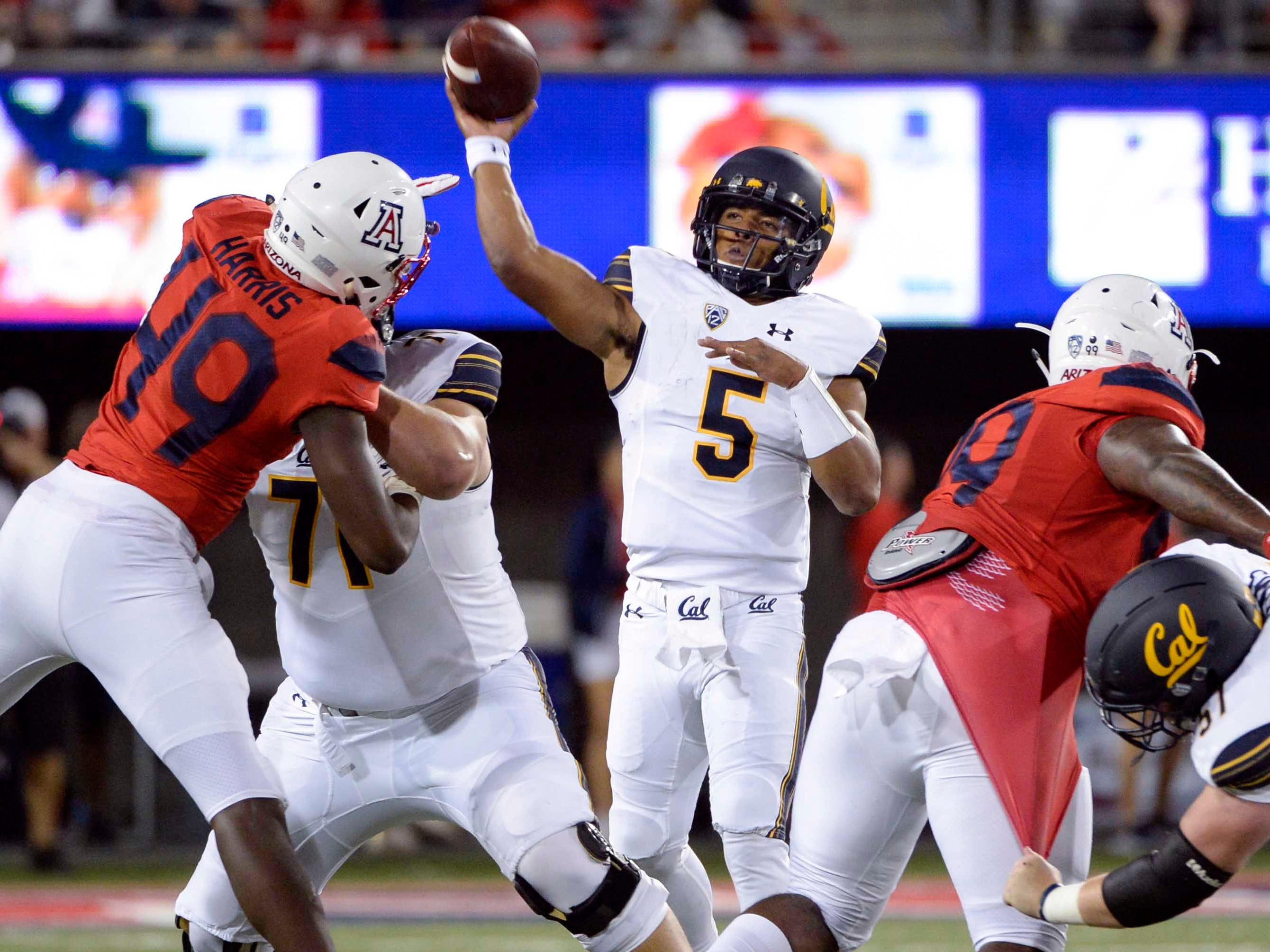 Oct 6, 2018; Tucson, AZ, USA; California Golden Bears quarterback Brandon McIlwain (5) passes the ball as Arizona Wildcats defensive end Jalen Harris (49) defends during the first half at Arizona Stadium. Mandatory Credit: Casey Sapio-USA TODAY Sports
