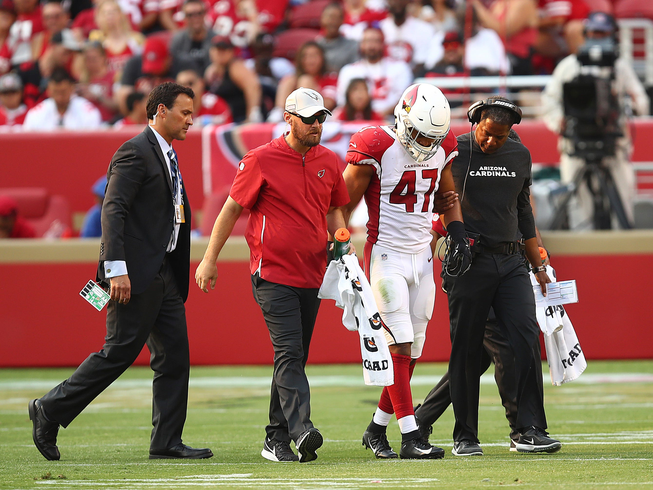 Arizona Cardinals linebacker Ezekiel Turner (47) is helped off the field by head coach Steve Wilks, right, and trainers during the second half of an NFL football game against the San Francisco 49ers in Santa Clara, Calif., Sunday, Oct. 7, 2018.