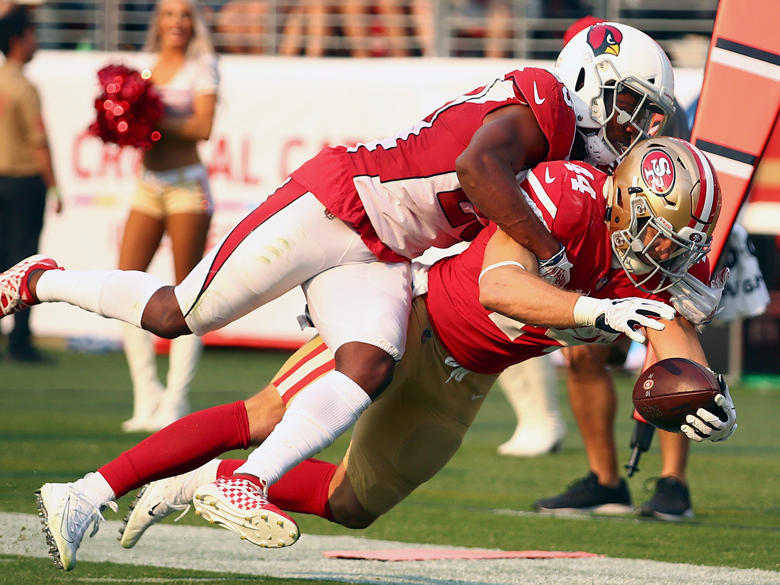 San Francisco 49ers fullback Kyle Juszczyk, bottom, is tackled by Arizona Cardinals defensive back Bene' Benwikere during the second half of an NFL football game in Santa Clara, Calif., Sunday, Oct. 7, 2018.