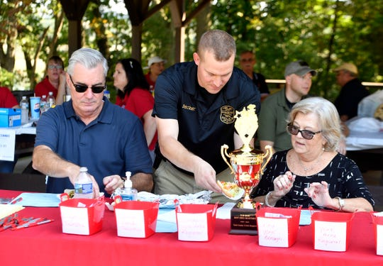Officer Cody Becker of Northern York County Regional Police Department serves Top Dog judges Chris Reilly, York County commissioner, left, and Senior Judge JoAnn Teyral walking taco hot dogs during the first  Top Dog Hotdog Contest, Sunday Oct. 7, 2018. John A. Pavoncello photo