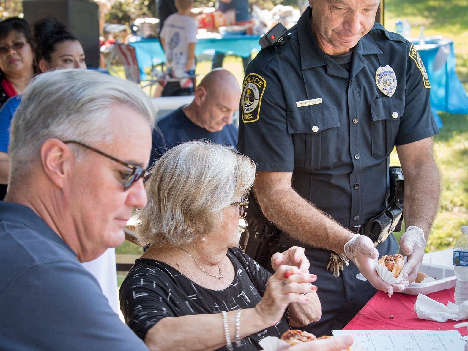 York Area Regional Patrolman Marc Greenly, right, hands over a 'Glazed and Confused' doughnut to judges Chris Reilly, left, and JoAnn L. Teyral, a senior magisterial judge during the recent York County Crimes Stoppers Top Dog Contest fundraiser at William Kain County Park.