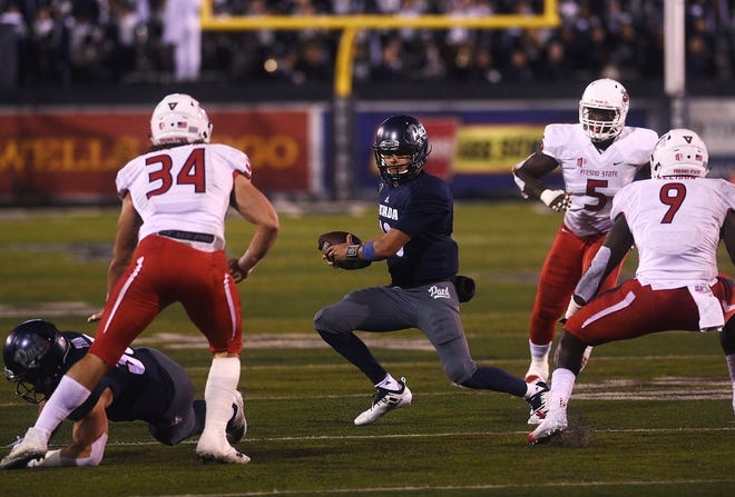 Nevada's Cristian Solano (13) looks for room to run against Fresno State on Saturday.
