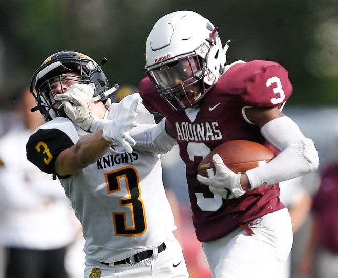 Aquinas' Damon Montgomery, right, stiff arms McQuaid's Andrew Passero during a regular season game played at Aquinas Institute, Saturday, Oct. 6, 2018. Aquinas and McQuaid are the top two seeds in the 2018 Section V Class AA Tournament.