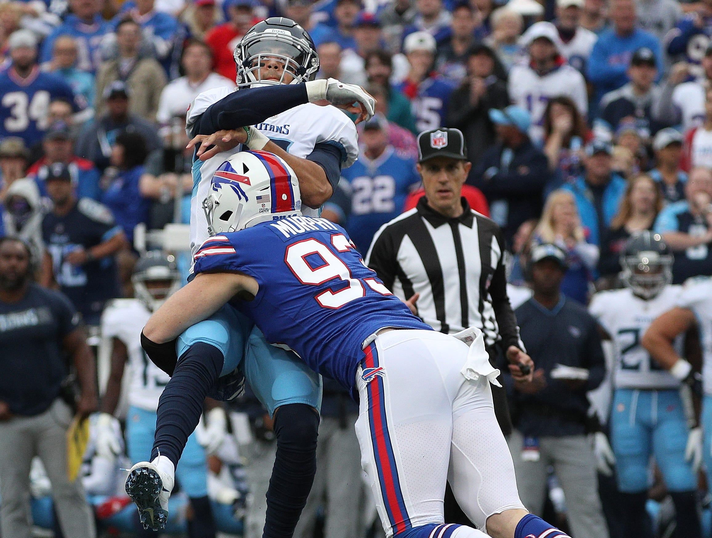 Bills Trent Murphy  hits Titans quarterback Marcus Mariota as he releases the ball.