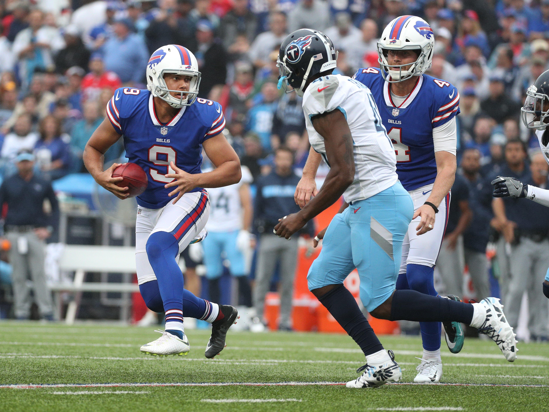 Bills holder Corey Bojorquez rolls away from pressure after a botched field goal attempt.