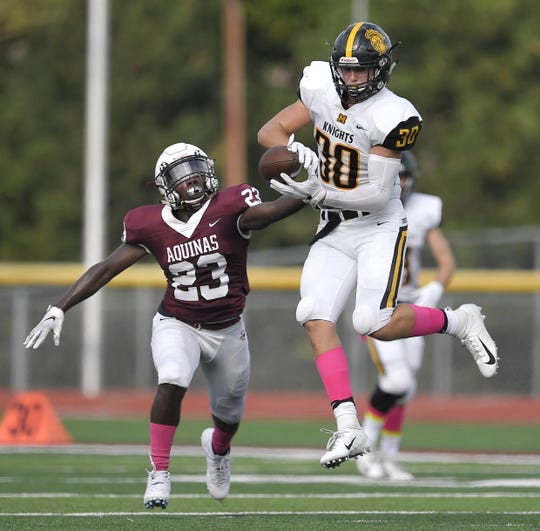 McQuaid's Connor Zamiara, right, catches a pass while covered by Aquinas' Juvon Johnson during a regular season game played at Aquinas Institute, Saturday, Oct. 6, 2018. Aquinas beat McQuaid 22-19.