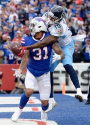 Tennessee Titans wide receiver Tajae Sharpe, right, reaches but is unable to make a catch as Buffalo Bills safety Dean Marlowe defends during the second half of an NFL football game, Sunday, Oct. 7, 2018, in Orchard Park, N.Y. (AP Photo/Adrian Kraus)