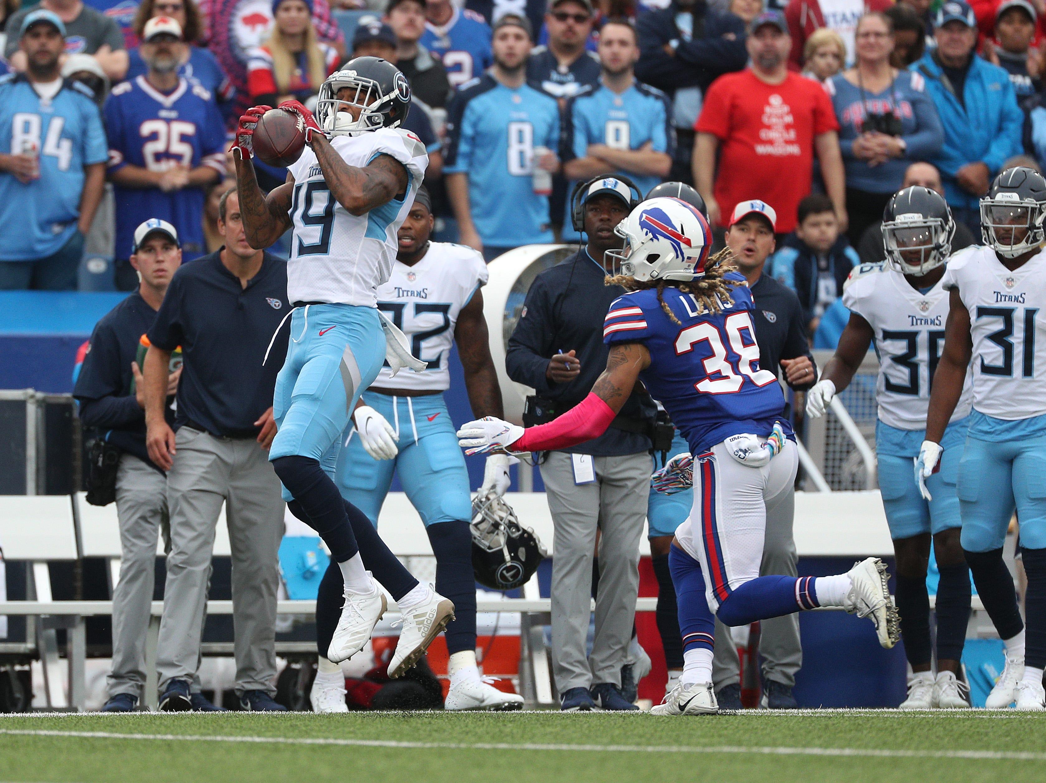 Titan's receiver Tajae Sharpe catches a pass in front pf Bills Ryan Lewis.
