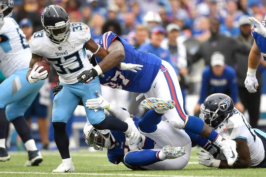 Tennessee Titans running back Dion Lewis (33) is tackled by Buffalo Bills defensive tackle Jordan Phillips, top, and defensive end Jerry Hughes during the first half of an NFL football game, Sunday, Oct. 7, 2018, in Orchard Park, N.Y. (AP Photo/Adrian Kraus)