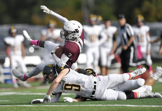 Aquinas' Damon Montgomery, top, is tripped up by McQuaid's Ben Beauchamp during a regular season game played at Aquinas Institute, Saturday, Oct. 6, 2018. Aquinas beat McQuaid 22-19.
