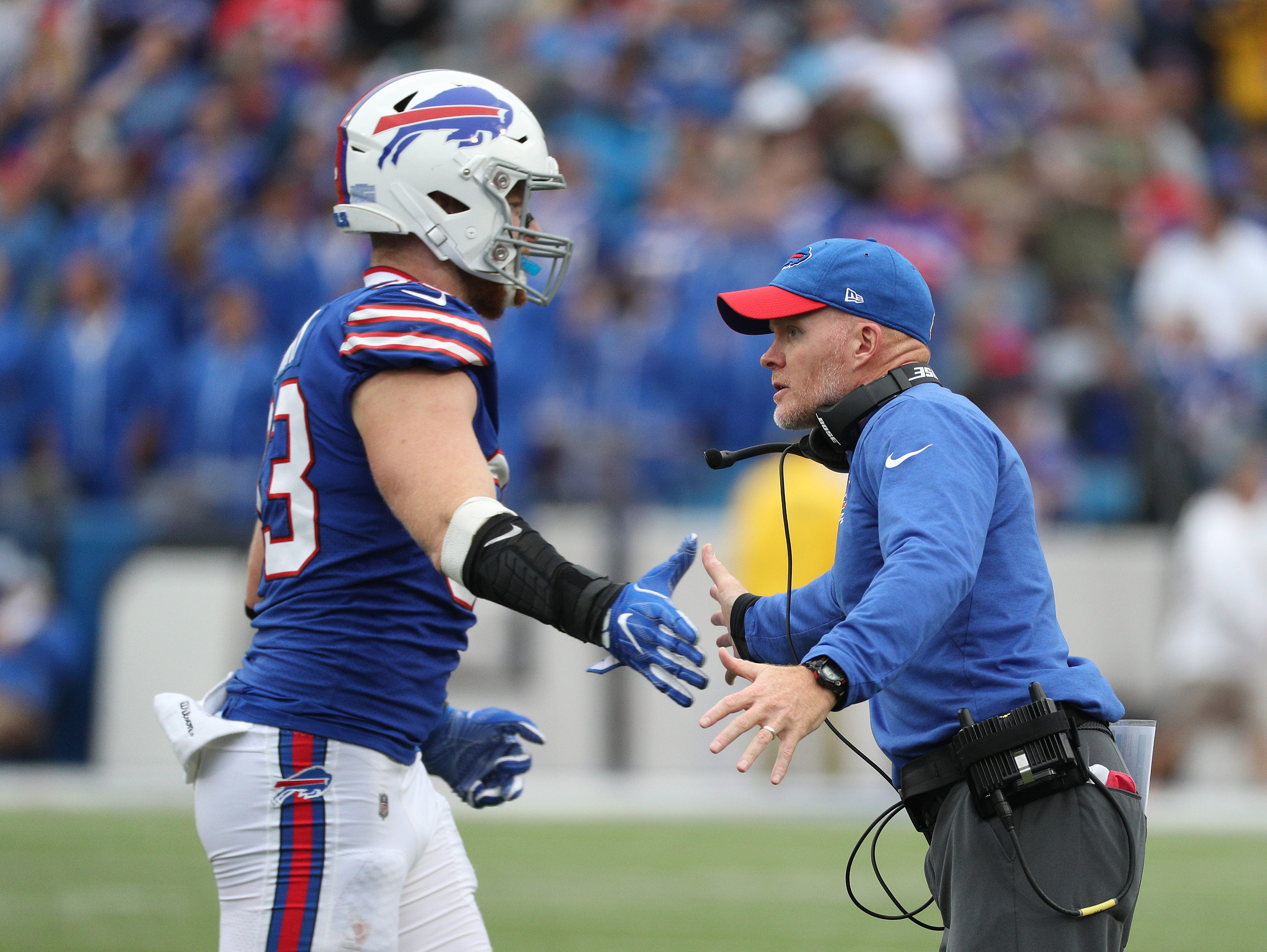 Bills head coach greets players as they come off the field after a defensive stop.