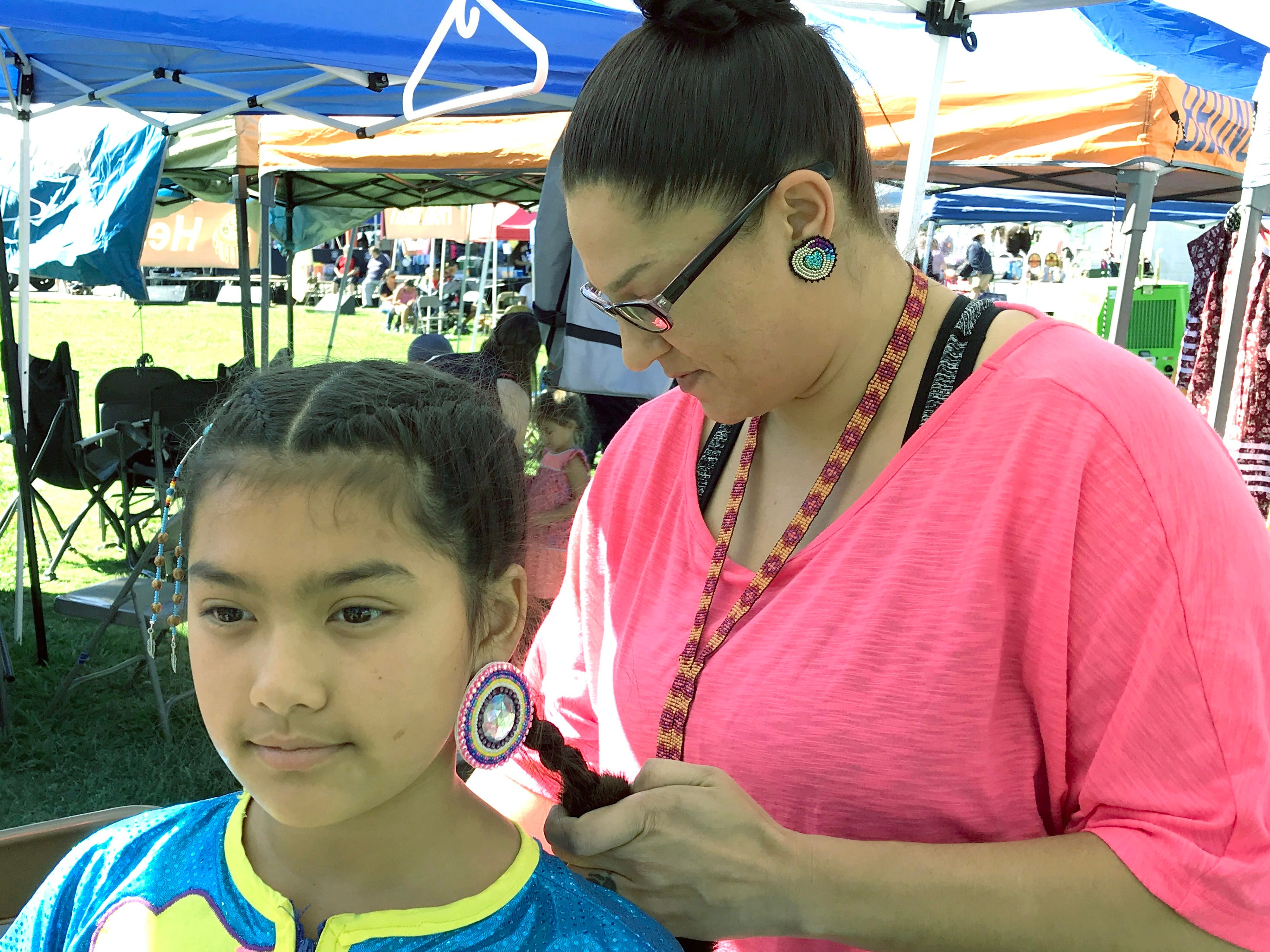 Patricia Riggins from Anderson, of Pit River and Wintu tribal heritage, does the hair of 11-year-old Dayjah Vue at the 2018 Stillwater Powwow at the Anderson fairgrounds. Dayjah is a jingle dress dancer.