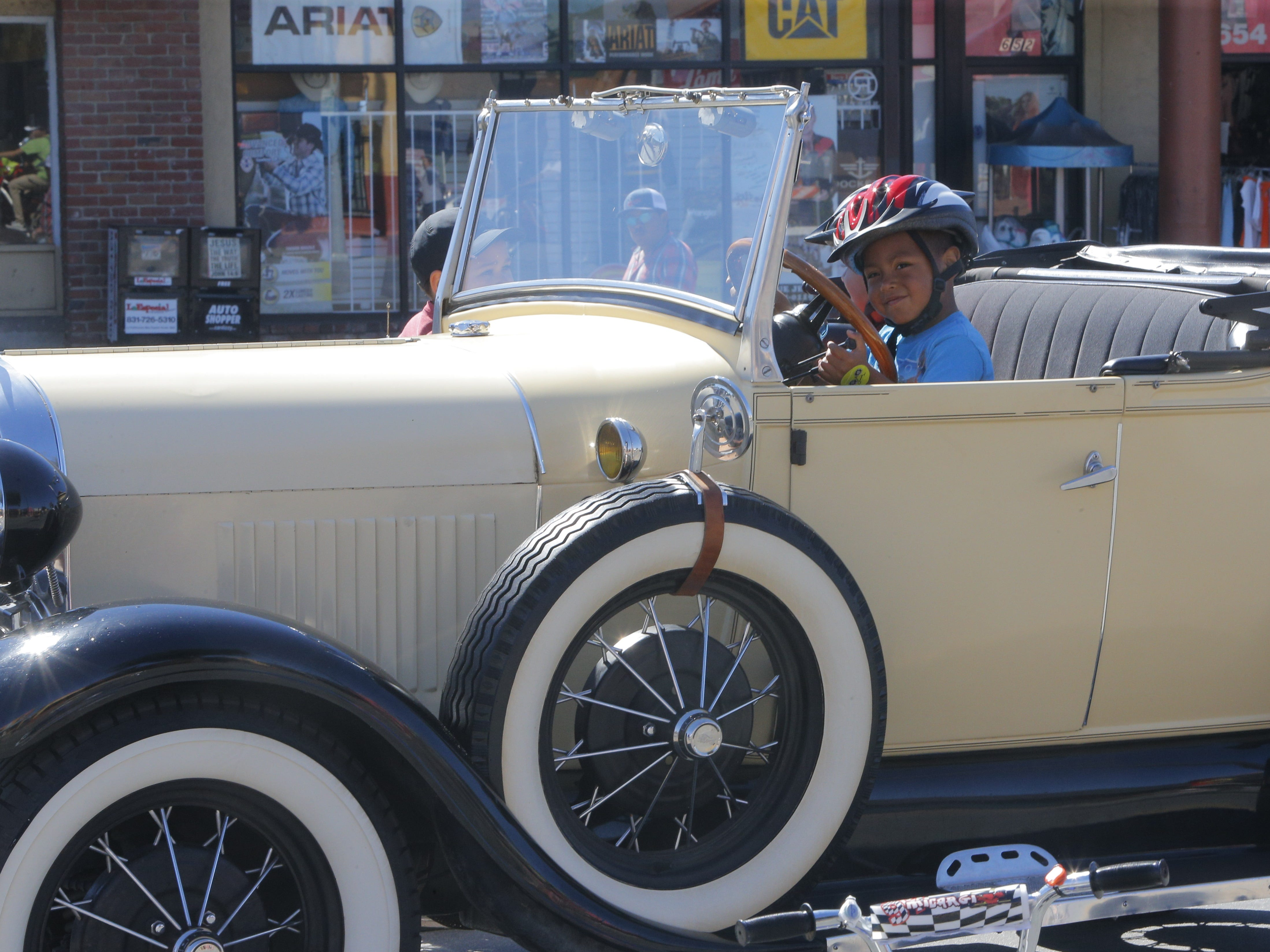 Dayron Flores, 5, models for a photo his mom is taking inside a classic car at the Ciclovia Salinas on Sunday.