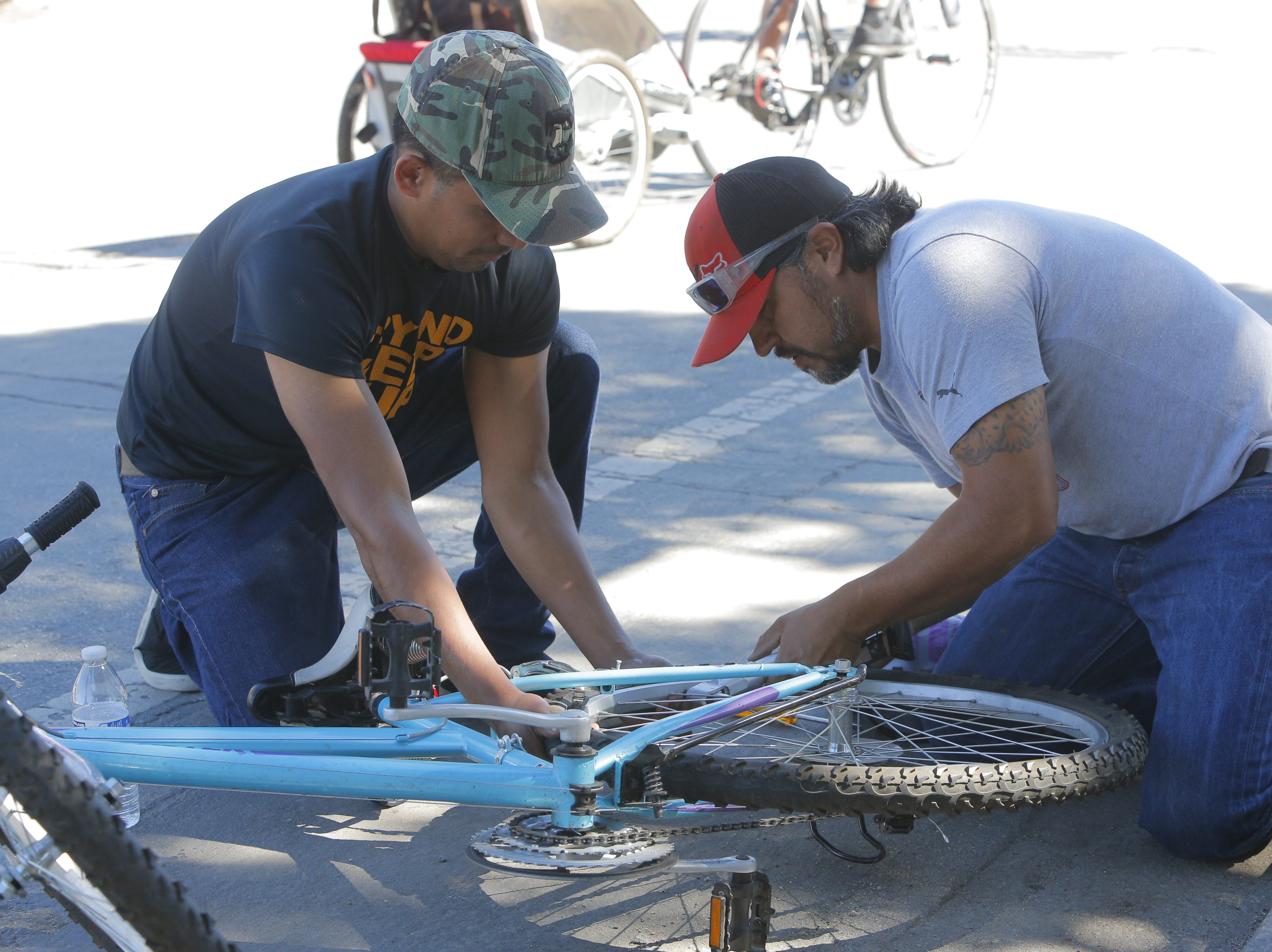 (From left:) Manuel Cruz, 29, an Ricardo Perez, 41, fix a bike tire during 2018's Ciclovia Salinas on E. Alisal Street Sunday.