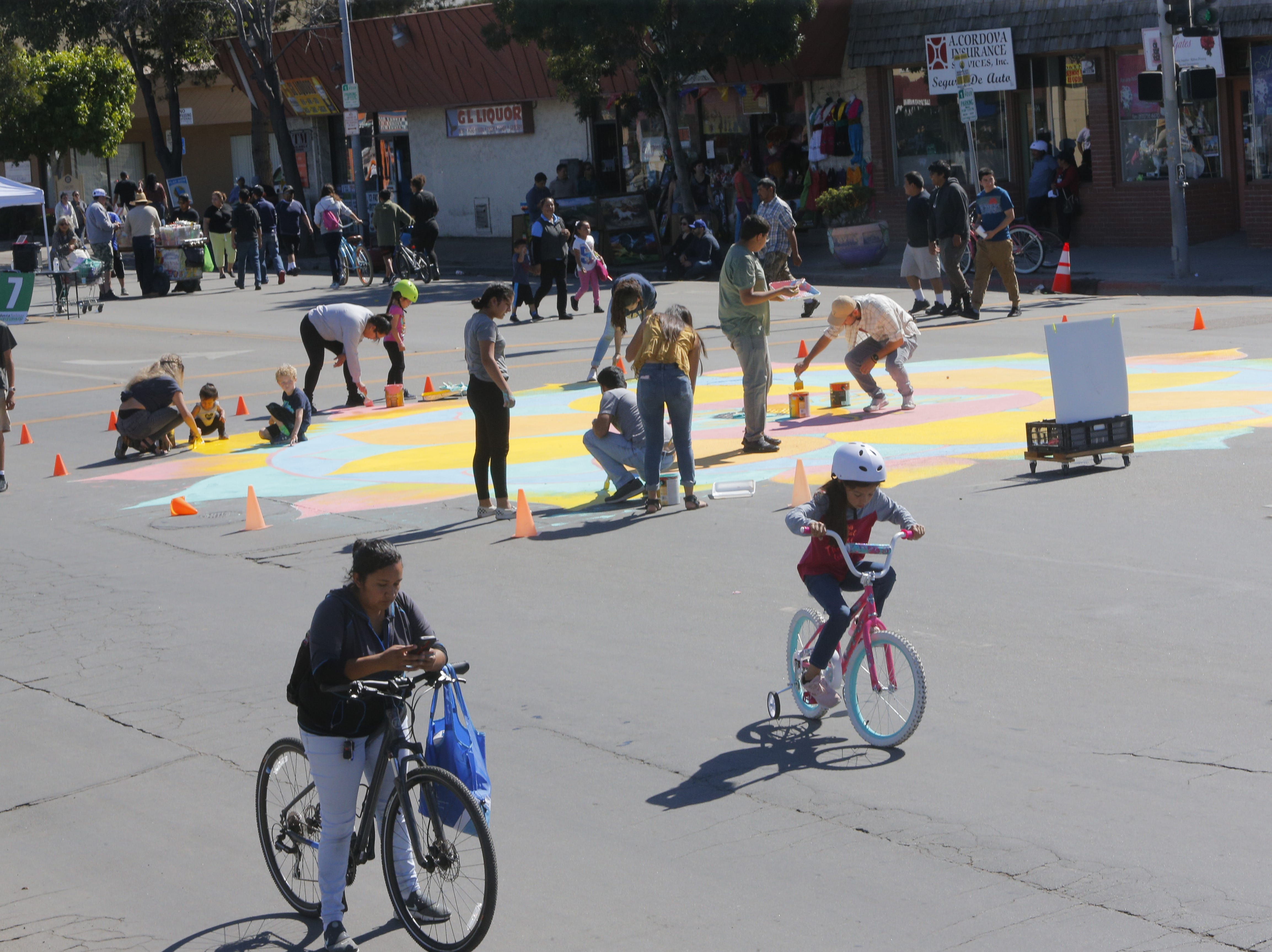 People paint the Ciclovia Mandala at 2018's Ciclovia Salinas on E. Alisal Street Sunday.