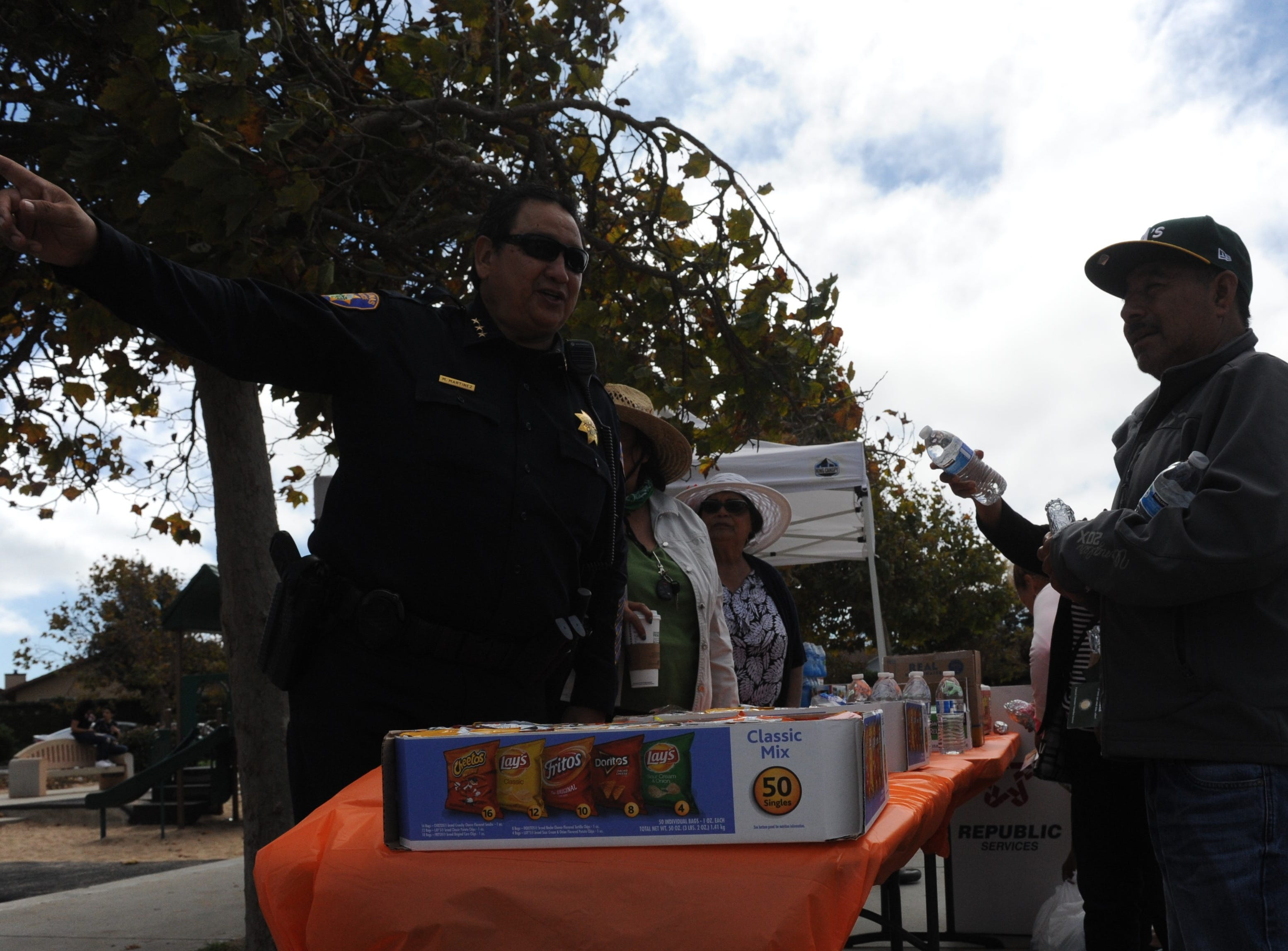 Assistant Chief of Police Manuel Martinez, left, speaks with Angel Mendoza, right, at the city's neighborhood block party at Soberanes Park on Saturday.