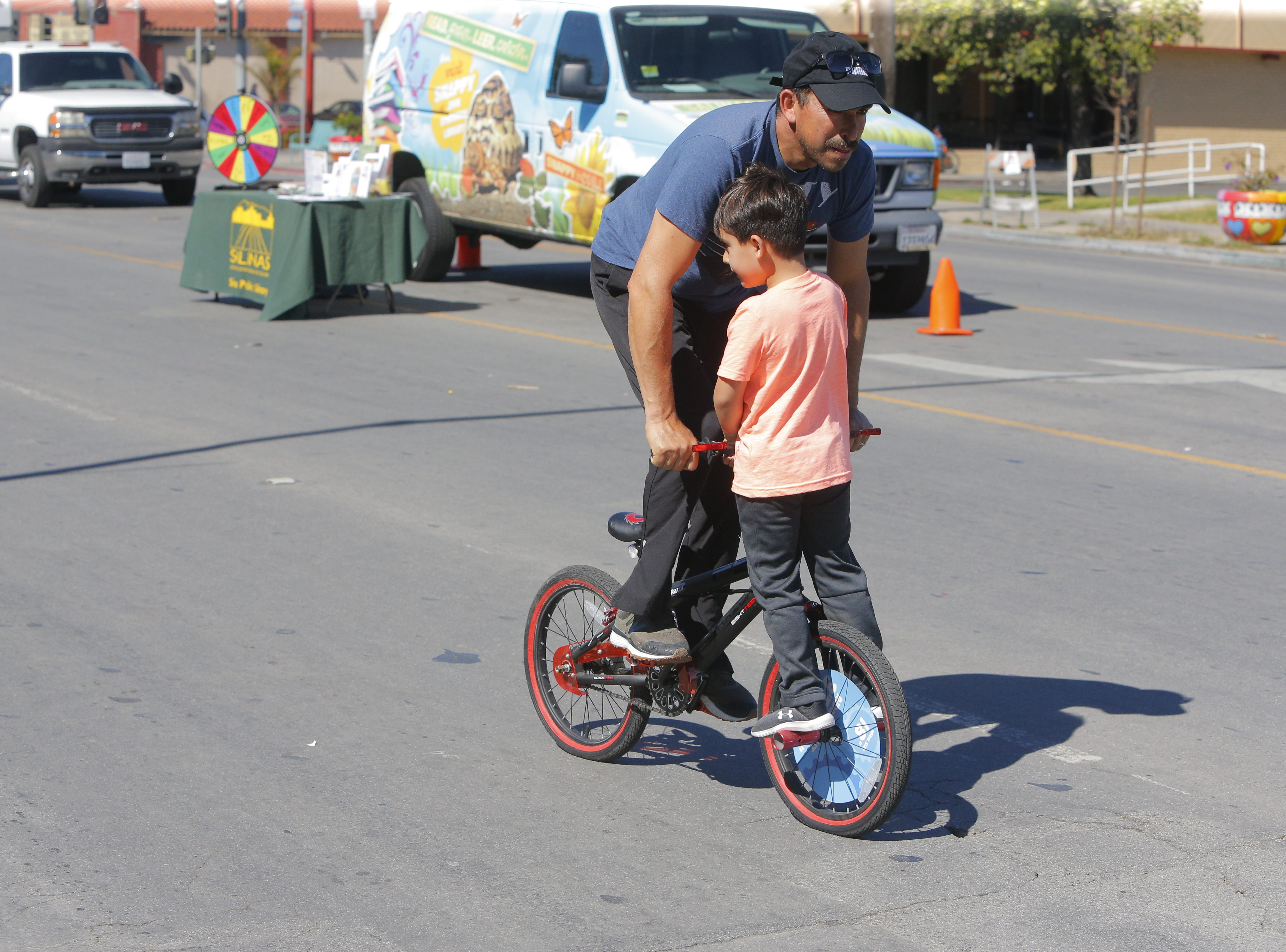 Salvador Ortega, 40, rides a bike wiht his son Pedro Ortega, 5, at 2018's Ciclovia Salinas on E. Alisal Street Sunday.