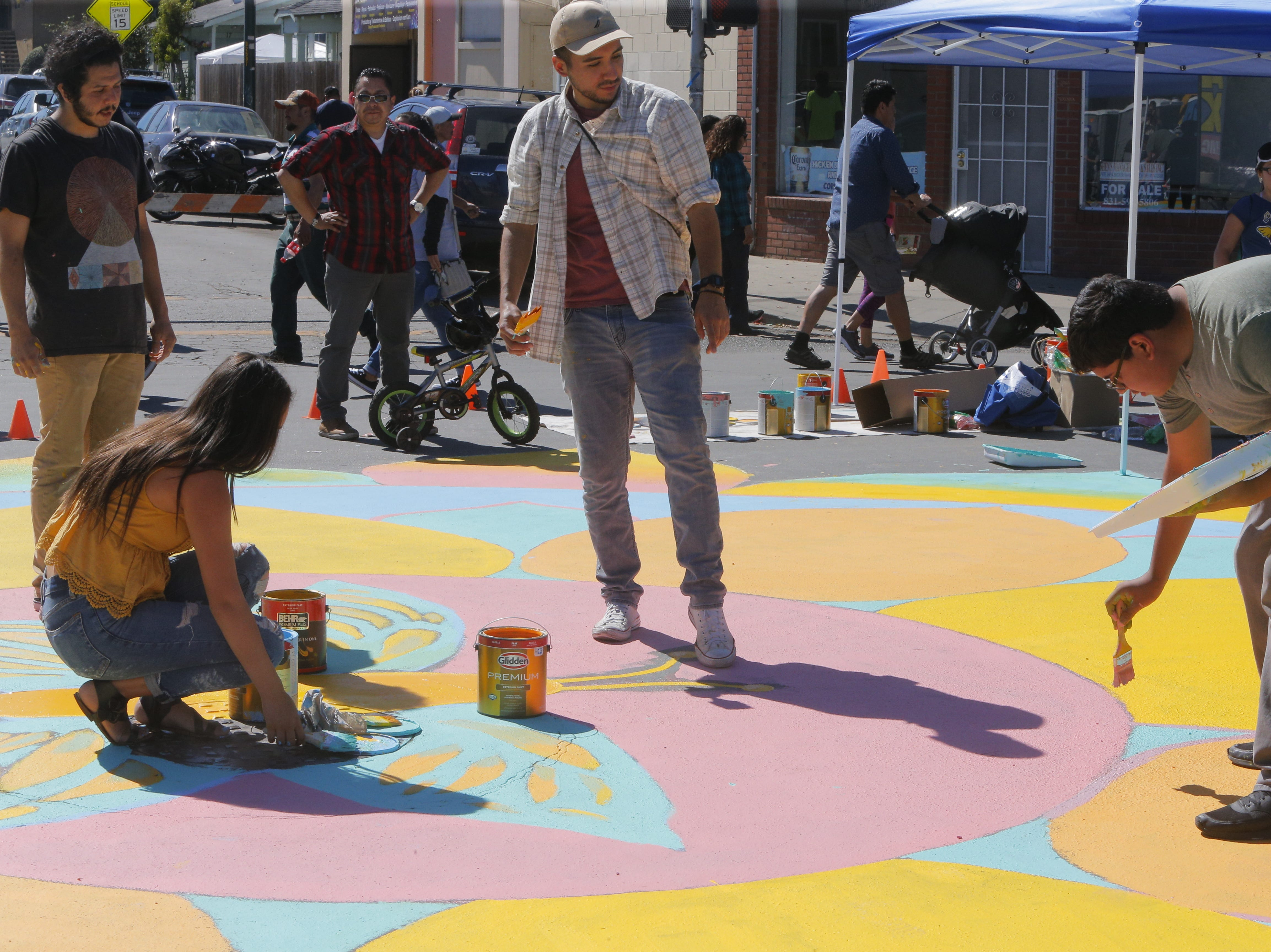 (From left:) Diana Renteria, Edwin Carillo and Arturo Renteria paint the 2018's Ciclovia Salinas Mandala on E. Alisal Street Sunday.
