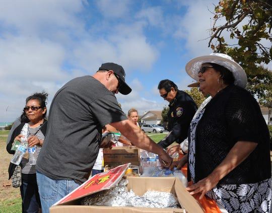 La concejal Gloria de la Rosa y Manuel Martínez, asistente del jefe de la policía, segundo de la derecha, entregan hot dogs, frituras y agua a los asistentes a la fiesta del vecindario organizada por la ciudad en el parque Soberanes.