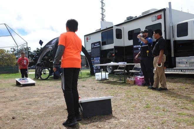 Dos jóvenes juegan mientras el sargento Kendall Gray, segundo de la derecha, y el voluntario de la policía Kevin Low, en el extremo derecho, los vigilan durante una fiesta de vecindario que se llevó a cabo en el parque Soberanes.